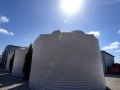 Three white water tanks with sun