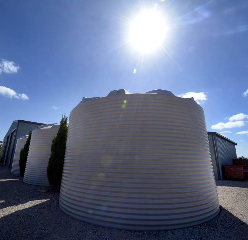 Three white water tanks with sun